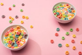 bright colorful breakfast cereal with milk in bowls on pink background