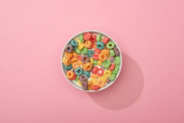 Top view of bright colorful breakfast cereal in bowl on pink background stock vector