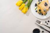 vrchní pohled na chutné palačinky s borůvkami a mátou na talíři u žlutých tulipánů a příbory na šedém pozadí