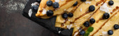 shora pohled na chutné palačinky s borůvkami, mátou a kokosovými vločkami podávané na palubě na texturovaném pozadí, panoramatický záběr
