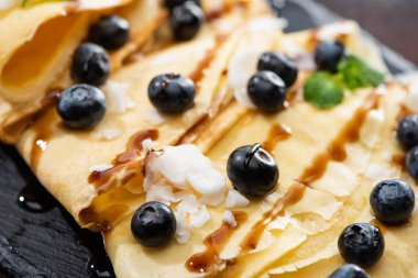 close up view of tasty crepes with blueberries, mint and coconut flakes
