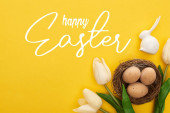 top view of tulips and chicken eggs in nest near Easter bunny on colorful yellow background with happy Easter illustration