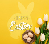 top view of tulips and chicken eggs in nest on colorful yellow background with happy Easter illustration