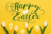 horní pohled na tulipány a malované velikonoční vajíčka na barevném žlutém pozadí s veselou velikonoční ilustrací