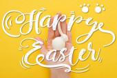 abgeschnittene Ansicht der Frau hält weißen Osterhasen auf bunten gelben Hintergrund mit glücklichen Ostern Illustration