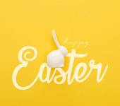 top view of white Easter bunny on colorful yellow background with happy Easter illustration