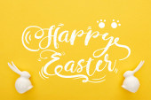 Fotografie top view of white Easter bunnies on colorful yellow background with happy Easter illustration