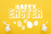 top view of white Easter bunnies on colorful yellow background with happy Easter illustration