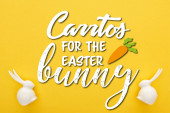 Fotografie top view of white Easter bunnies on colorful yellow background with carrots for the easter bunny illustration