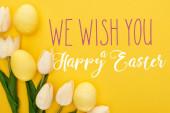 Fényképek felső nézet tulipán és festett húsvéti tojás színes sárga háttér kívánunk boldog húsvéti illusztráció