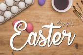 Draufsicht auf Aquarell lila Farbe in Schale in der Nähe bemalter Hühnereier und Pinsel auf Holztisch mit frohen Ostern Illustration