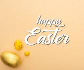 Fotografie Draufsicht von Bonbons, Wachteln und Schokoladeneiern auf beigem Hintergrund mit frohen Osterbildern