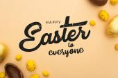 Ansicht von Schokolade und Wachteleiern mit gelben Bonbons auf beige mit frohen Ostern für alle Abbildung