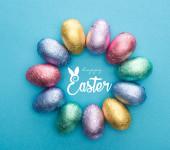 Draufsicht des Kreises mit Schokoladen-Ostereiern in bunter Folie auf blauem Hintergrund mit frohen Osterbildern