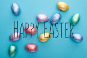 Photo Top view of chocolate Easter eggs on blue background with happy Easter illustration