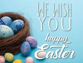 Fészek és színes csirke és fürj tojás kék alapon kívánunk boldog húsvéti illusztrációt
