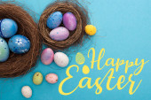 Fotografie Top view of colorful Easter eggs in nests on blue background with happy Easter illustration