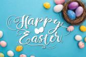 Horní pohled na barevné kuřecí a křepelčí vejce s hnízdem na modrém pozadí s veselou velikonoční ilustrací