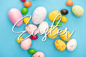 Horní pohled na světlé barevné sladkosti a velikonoční vajíčka na modrém pozadí s velikonoční ilustrací