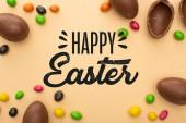 Fotografie Draufsicht auf Schokoladeneier und leckere Süßigkeiten auf beigem Hintergrund mit frohen Osterbildern