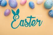 Draufsicht auf lila Hühnereier auf beigem Hintergrund mit frohen Ostern Illustration