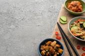 vrchní pohled na mísy s chutnými kimchi v blízkosti hůlek, nakrájené okurky a chilli paprikou na pytlovině na betonovém povrchu