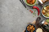 Fotografie vrchní pohled na chutné kimchi v miskách a sklenicích, v blízkosti hůlek a chilli papriček na betonovém povrchu