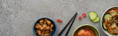 panoramatický záběr misky s lahodnými kimchi v blízkosti nakrájené okurky a hůlky na betonovém povrchu