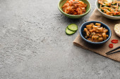 misky s kimchi na pytlovině v blízkosti hůlek, krájený česnek, okurka a chilli paprika na betonovém povrchu