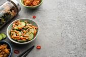 chutné kimchi v miskách a sklenicích v blízkosti hůlek na betonovém povrchu