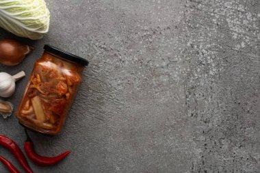 Kimçi kavanozunun üst görüntüsü, kırmızı biber, sarımsak, soğan ve çimentoda Çin lahanası.
