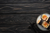 top view of plate with korean gimbap and chopsticks on wooden surface