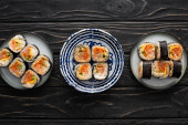 top view of plates with tasty and korean gimbap on wooden surface