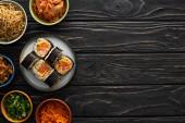 vrchní pohled na talíř s čerstvým gimbapem v blízkosti korejských bočních misek na dřevěném povrchu