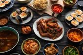 talíře a mísy s korejskými bočními talíři a gimbap na dřevěném povrchu