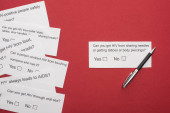 top view of paper cards with HIV questionnaire and pen on red background