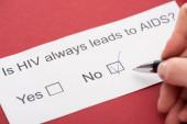oříznutý pohled na osobu, která odpovídá na dotazník HIV na červeném pozadí
