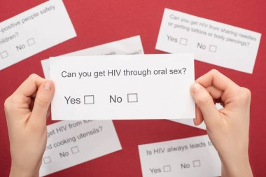 partial view of woman holding HIV questionnaire on red background