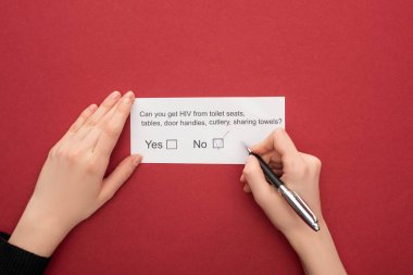partial view of woman answering HIV questionnaire on red background