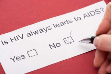 cropped view of person answering HIV questionnaire on red background