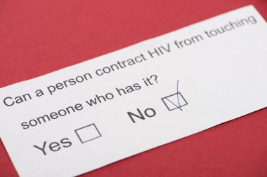 paper card with HIV questionnaire on red background