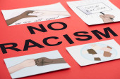 Fotografie black no racism lettering among pictures with multiethnic hands on red background