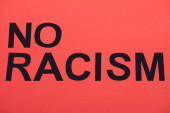 Fotografie top view of black no racism lettering isolated on red