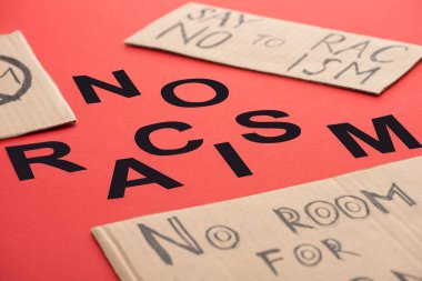 black no racism lettering among carton placards on red background