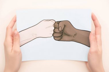 cropped view of woman holding picture with drawn multiethnic hands doing fist bump on beige background