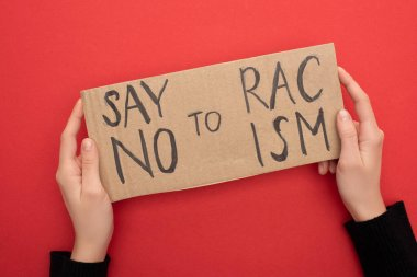 cropped view of woman holding carton placard with say no to racism lettering on red background