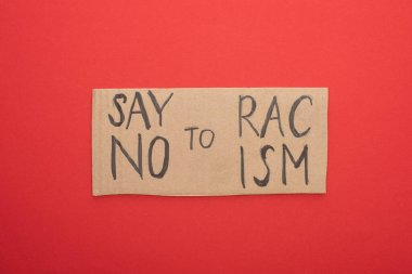 top view of carton placard with say no to racism lettering on red background
