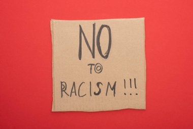 top view of carton placard with no to racism lettering on red background