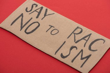 carton placard with say no to racism lettering on red background