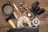 Photo top view of hiking rope, axe, binoculars, knife, carabiners, compass, iron mug and gas burner on wooden table